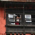 窓から雨を眺める子ども